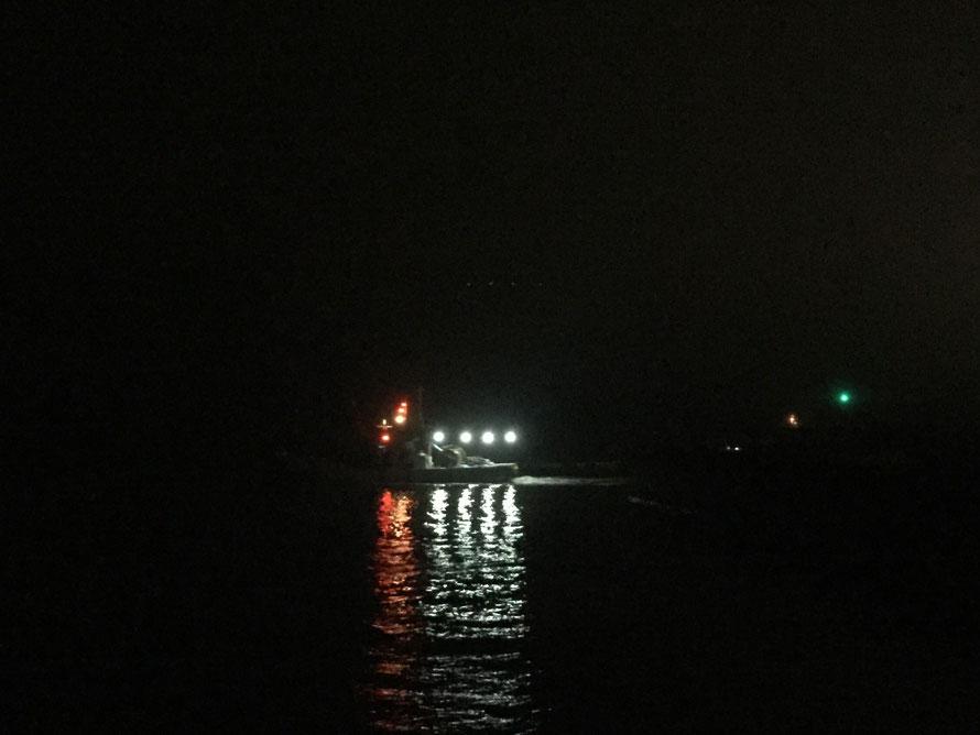 照明のたくさんついた漁船が真っ暗な海へ出ていきます。