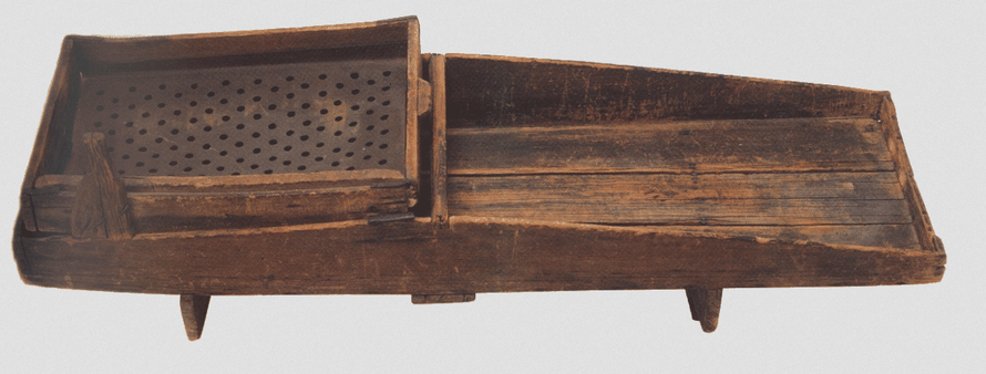 A gold cradle: gravel is placed in the box with holes and rocked with water pouring on it. Dust is supposed to fall onto the bottom part of the cradle and be caught by a piece of blanket laid on it (c