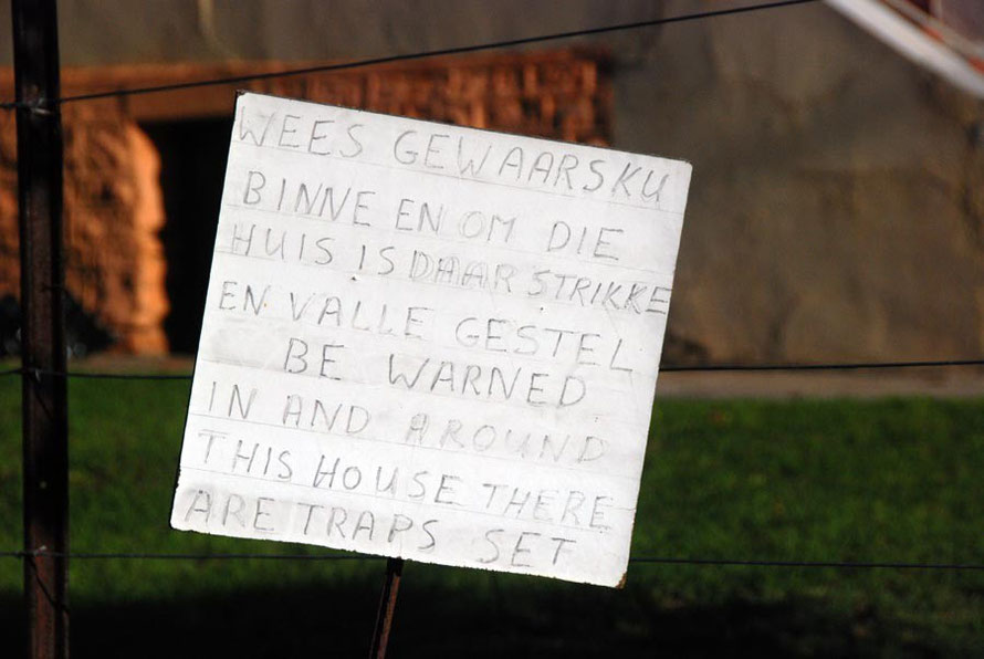 Bi-lingual, handwritten sign in a garden in Montagu warning of traps set in and around the house