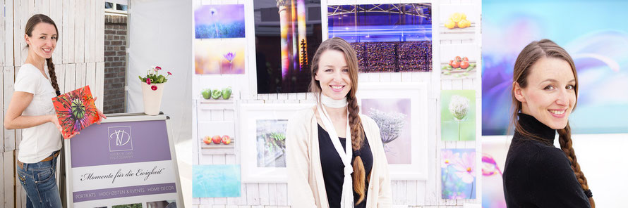 Junge Frau, lange mittelbraune geflochtene Haare, steht vor Fotobilderwand, lächelt in Kamera, hält ein Bild in der Hand