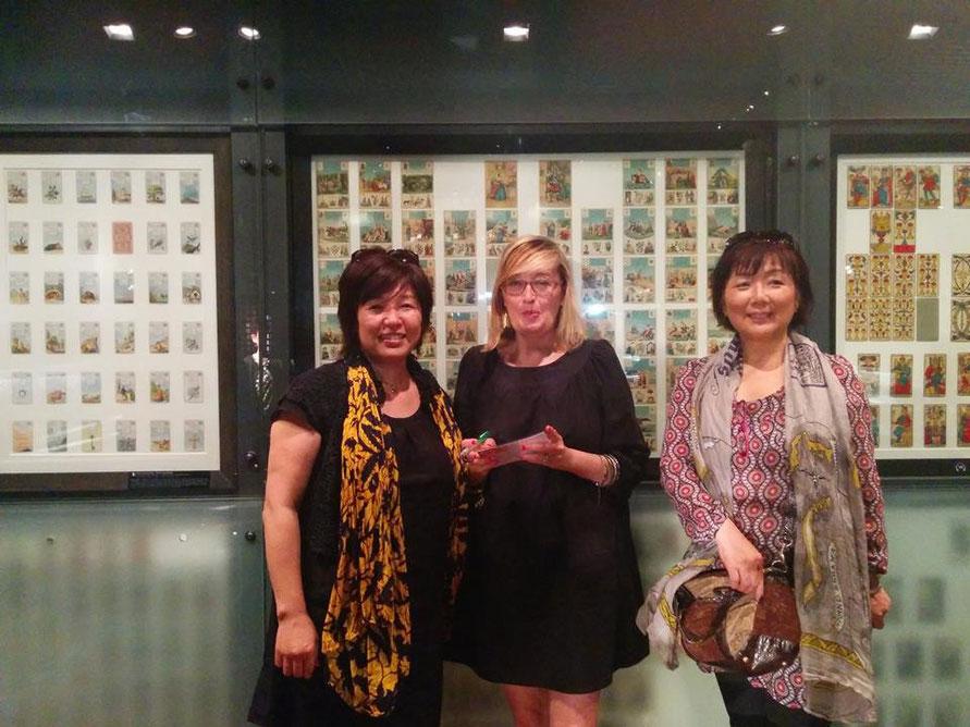ルノルマン グラン・ジュ―のカードが展示されている前で、通訳のMIKAさん、案内をしてくれたカトリーヌさんと小宮ベーカー純子
