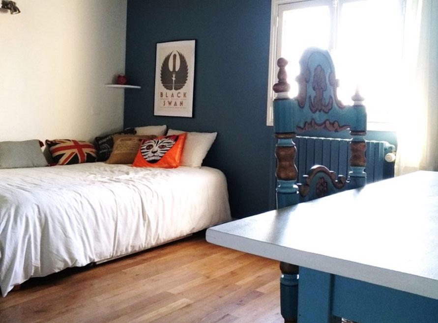 Chambre d'ado mansardée gris bleuté, blanc crème, parquet en chêne cérusé, affiche de cinéma, chaise catalane relookée, coussins colorés orange et bleu, rideau écru en coton épais.