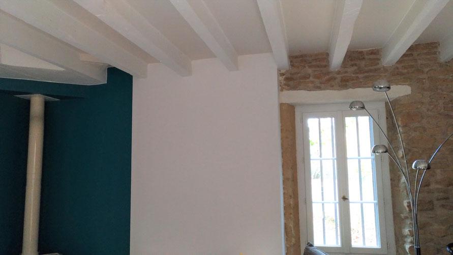 Intérieur avec pierres apparentes et poutres repeintes en blanc. Murs peints en bleu et poêle en céramique.