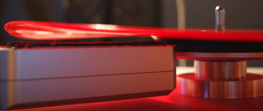 Eine rote, verwellte Schallplatte auf der Plattenwaschmaschine