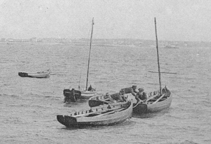 Cinq péniches au mouillage à l'entrée du port, trois n'ont pas de mât