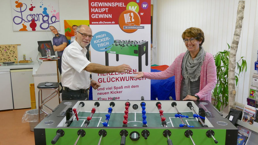 Aus der Hand von Die 2-Chef Uwe Kanacher nimmt Quickborns Stadtjugendpflegerin Birgit Hesse den Start-Ball für das erste Spiel am neuen Tischkicker entgegen.
