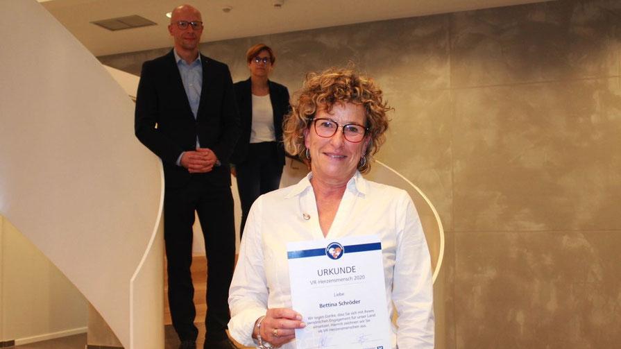 Jens-Hartwig Göttsch (Bereichsleiter VReG Region Norderstedt) und Kathleen Röpke (Mitarbeiterin Marketing VReG) freuen sich mit Bettina Schröder über die Auszeichnung