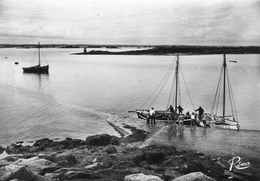 Le débarcadère  de l'île aux Moutons dans les années 60, les bateaux de passage sont mixte voile et moteur le long de la cale en blanc le sloop Saint-Pierre Mx 2680 à Jean Cabioch et la petite gabare à cul pointu Saint-Yves  et au mouillage La Fauvette