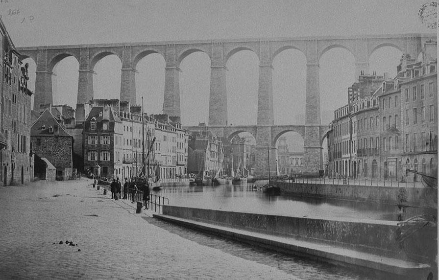 Vue du fond du port de Morlaix vers 1865, le bassin arrive au pied du viaduc construit entre 1861 et 1863, de grand lougres de cabotage déchargent et chargent en pleine ville