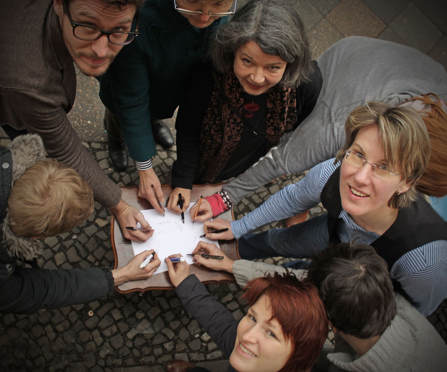 Auf dem Foto: die Hände der lesenden AutorInnen - einen Stift haltend um Großes zu schreiben