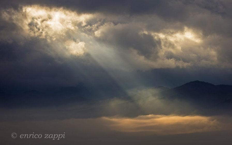 Raggi di luce solare, alla stregua di luci laser, hanno penetrato le nubi sopra il Carnaio andandosi a infrangere sulla coltre nebbiosa della vallata, senza scalfirla.