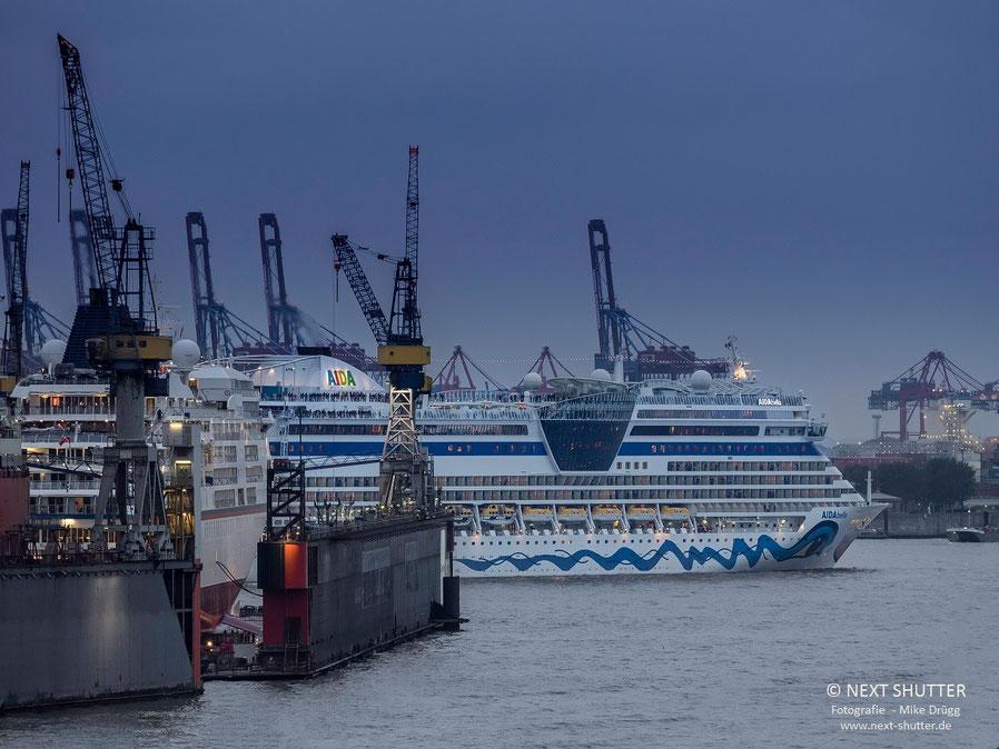 AIDAbella hat das Steinwerder Cruise Center für eine neue Reise verlassen. Links im Dock : die Europa von Hapag - Lloyd Kreuzfahrten.