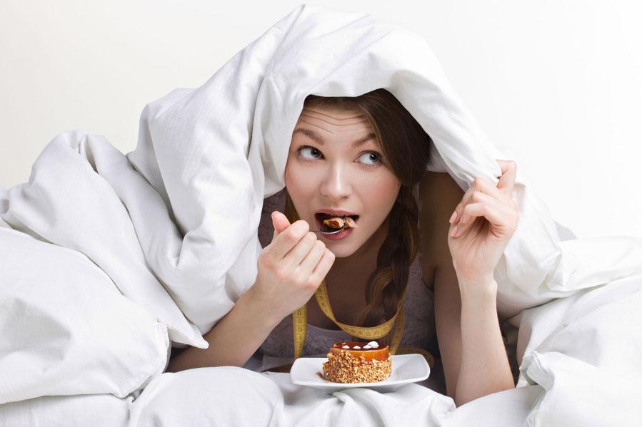 Frau isst heimlich unter der Decke