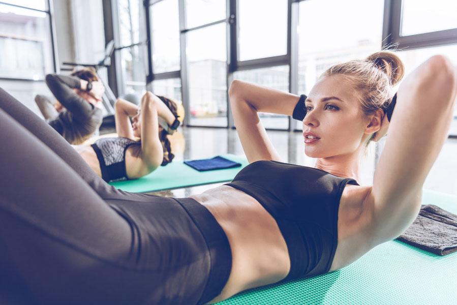 Frauen trainieren Bauch im Fitnessstudio