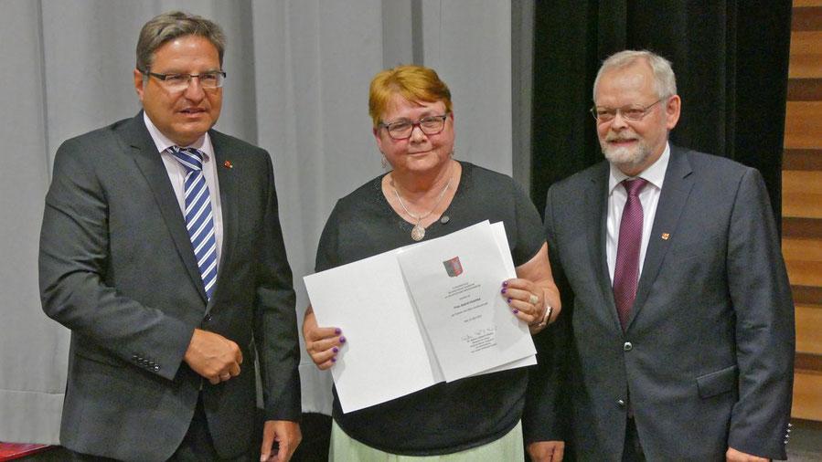 Nach der Laudatio durch Bürgervrorsteher Henning Meyn (r.) überreichte Bürgermeister Thomas Köppl die Urkunde an Astrid Huemke