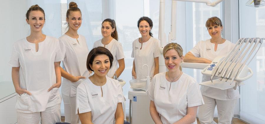 Zahnärzte, Dentalhygienikerin und Dentalassistenten im Behandlungsraum