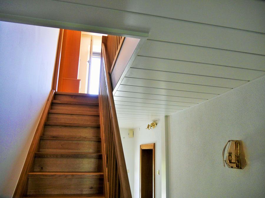 Stiege und Geländer in Eiche massiv, Natur lackiert, Deckenpaneele und Leisten in Esche weiß lackiert (offenporig)