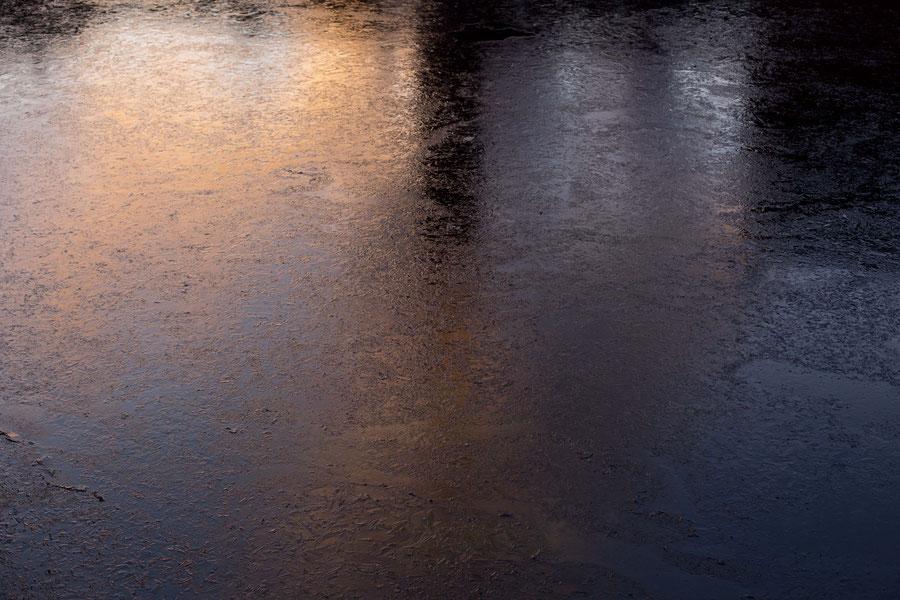 Auf einer dünnen Eisschicht reflektierendes Abendlicht, Tampere, Finnland