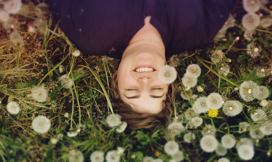 Woman in a field of flowers, grinning.