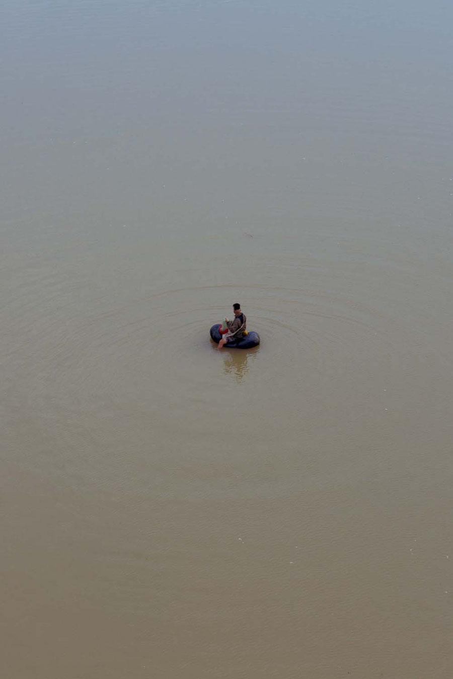 Fischer auf Gummiboot, Jinghong, China
