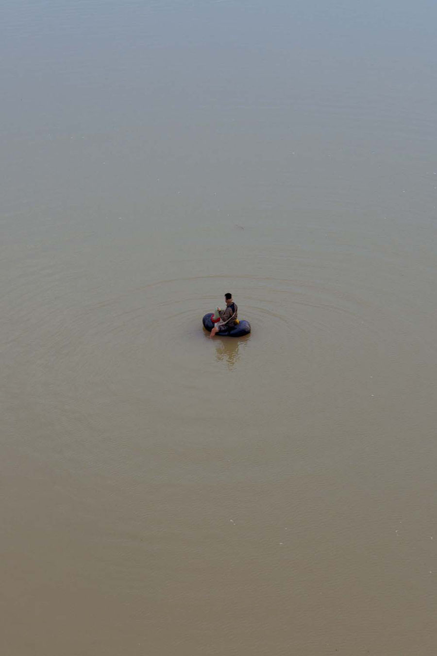 A fisher in the mekong with his tiny toy boat, Jinghong, China