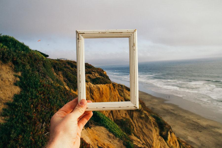 Auf dem Bild ist eine Hügellandschaft und das mehr abgebildet. Ein Bilderrahmen wird hochgehalten. Für weitere Informationen bitte die Bildunterschrift lesen.