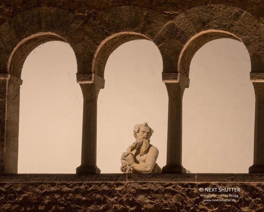 Der Wächter ist  Gottvater Zeus, er scheint sich lässig über die Brüstung zu lehnen.