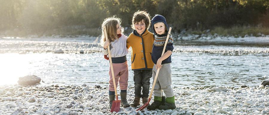 kinder in rosa und grauer walkhose, curryfarbener walkjacke und blauer walkmütze für kinder aus merinowalk, nachhaltig produziert