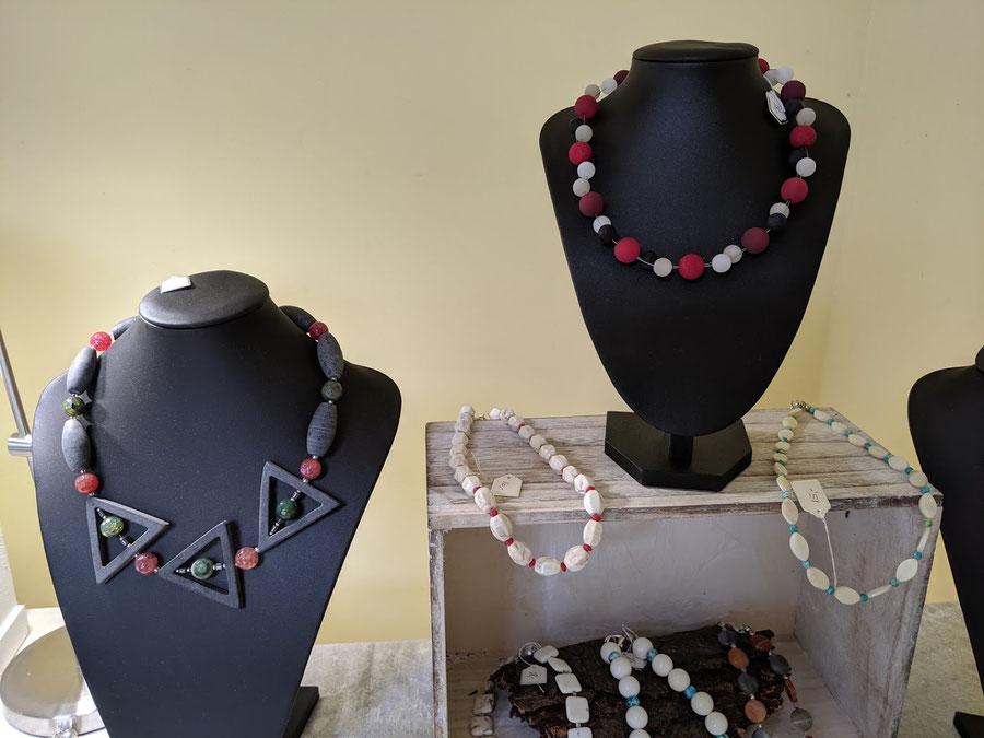 Das Bild zeigt die Dekoration zweier Damenketten, die jeweils auf einer Schmuckbüste präsentiert werden. Eine Kette wurde aus Achat-Perlen kombiniert mit Onyx-Walzen und Onyx-Dreiecken. Die zweite Damenkette besteht aus Polaris-Perlen.