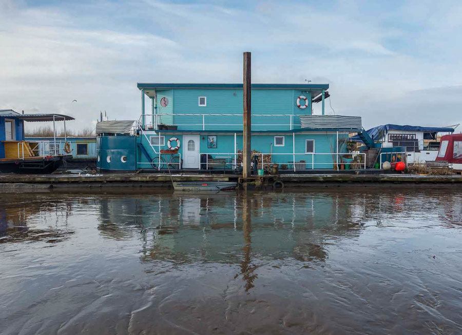 houseboat in Timber Port (Noun) at low tide in the river elbe. Hafenlieger mit zwei Stockwerken und Balkons.© Christian Kaiser
