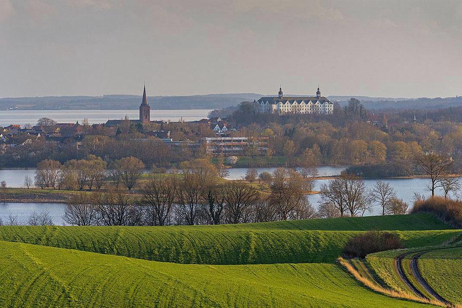 Blick über Wiesen, Felder und Knicks auf den kleinen Plöner See mit dem Schloss Plön, heute Fielmann Akademie.