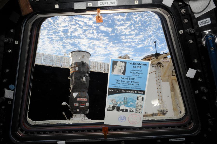 Ein Fenster der CUPOLA ISS mit Ausstellungsflyer vor der Erdkugel und dem Sojus Raumschiff.