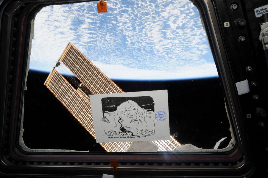 Die Grafik von Reinhard Lakomy vor dem Fenster mit Blick auf die Erde