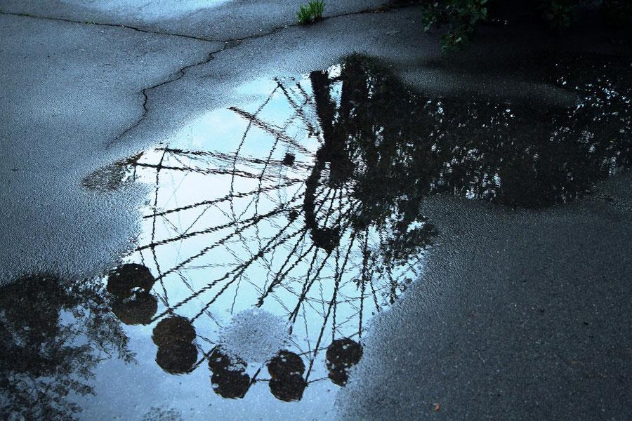 Spiegelung des Riesenrads auf dem mit 14 Mikrosievert pro Stunde strahlenden Asphalt