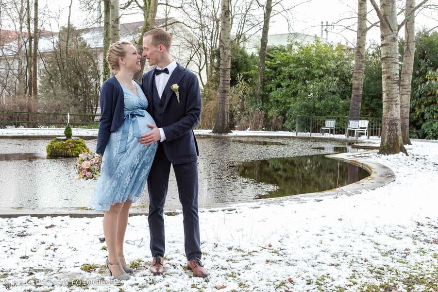 Brautpaar schwanger im Schnee im Garten vom Schloss Bümpliz