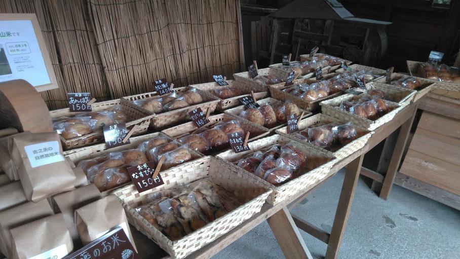 ▲2019年9月中旬に撮ったパンの写真。この日は全18種類の米パンで、さつまいも、かぼちゃ、ポテサラ、玉ねぎ、山椒チーズ、青じそチーズ、丹波黒豆、ガーリック、なすび、きゅうちゃん、玄米、万願寺パンが無農薬・自家栽培の野菜を使った米パンでした。ちなみに生地は無農薬・自家栽培の美山米80%と小麦グルテン20%です。この日、具材を購入したパンはレーズンぱん、チョコぱん、チーズぱん、きなこ揚げぱん、あんぱんになります。以前は小豆もつくってたけど猿にやられることが多く、今は北海道小豆を買って甘さ控えめで炊いてます。