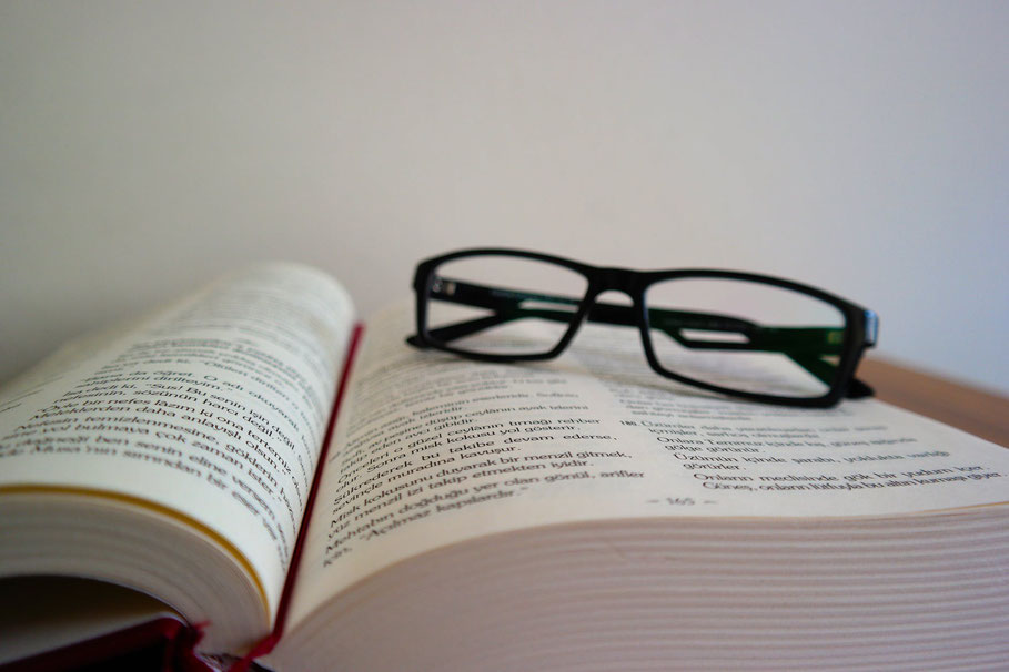 Brille und offenes Buch