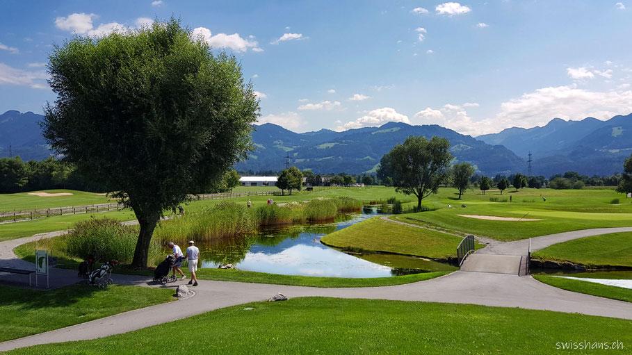 Golfplatz Rankweil mit kleinem See, Baum und Golfspieler