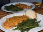 Schweinskoteletts in Paprika-Sauce mit grünen Bohnen angerichtet