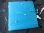 Fotoalbum/Gästebuch zum 50. Geburtstag - 25cmx25cm, 100 Seiten weiß, Bezugstoff: Taft blautürkis, Buchschmuck: Perlen weiß und rose, Schleifenverschluss silbergrau, Stickerei: Name.