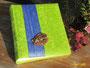Fotoalbum - 25cmx30cm, 100 Seiten weiß, Bezug: Samt hellgrün, Buchschmuck: vertikale Borte in Blau mit lackierter Echtholz-Applikation.