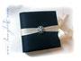 Tagebuch - 24cmx24cm, 100 Seiten elfenbeinfarben, Bezugstoff: Crashtaft dunkelblau, Buchschmuck: umlaufender Schleifenverschluss cremefarben, Zier-Brosche.
