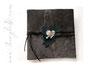 Dunkelbraunes Lederalbum mit Blättern aus dunkelgrünem Leder, großem Herzanhänger, umlaufendem Flachlederband und petrolfarbenen Perlen.