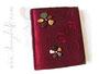 Fotoalbum Feuer & Stein - 25cmx30cm, 100 Seiten, Bezugstoff changierender Crashtaft rot, antikmessingfarbene Buchecken aus Metall, Buchschmuck: Blumen aus lackierten Steinen.