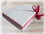 Notizbuch mit wechselnden Lagen farbigen Blankopapiers und Schleifenverschluss