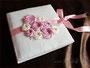 Romantisches Fotoalbum zur Hochzeit mit einem Einband aus Lingerie (Spitzenstoff), dekoriert mit Stoffrosen und Schleifenverschluss in den Farben creme, rosa und pink.