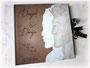Fotoalbum mit Silhouetten des Paares aus Strukturpapier, beschriftetem Cover und Schleifenverschluss