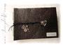 Fotoalbum Echtleder-Einband in antik-schwarz-braun mit großem Herzanhänger als Buchverschluß, kleinem Schlüssel,  2 Zahnrädern und Glöckchen, sowie mit Namen graviertem Metallschild. Format 35cm x 25cm.
