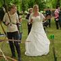 Das Brautpaar lernt Bogenschießen.