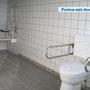 Ein barrierefreies Badezimmer mit Dusche, Toilette und Waschbecken